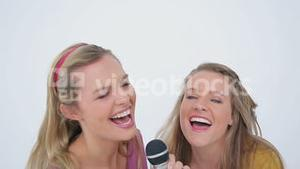 Friends jumping and singing in a microphone