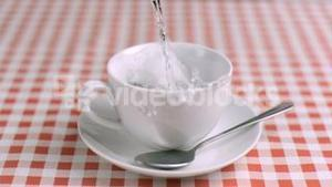 Water being poured in super slow motion into a cup