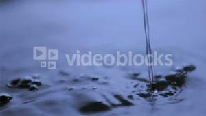 Water flowing in super slow motion into water