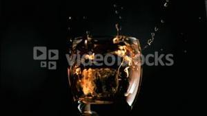 Ice cube falling in super slow motion in whiskey