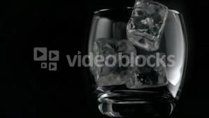 Ice cubes falling in super slow motion in a glass