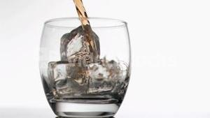 Whiskey poured in super slow motion in a glass with ice cubes