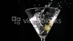 Olive skewer falling in super slow motion in a glass