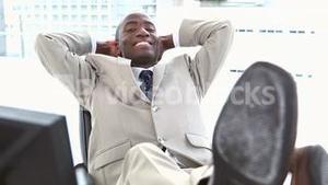 Black businessman the feet on his desk