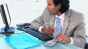 Latin businessman using a calculator