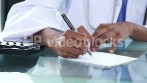 Black doctor writing a note