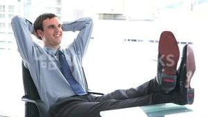 Businessman at ease the feet on his desk