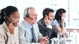 Serious call centre agents talking with headsets