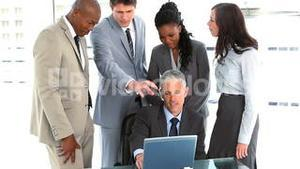 Colleagues helping a businessman with his laptop