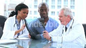Serious doctors and an intern looking at an xray