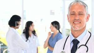 Happy mature doctor standing in front of his team