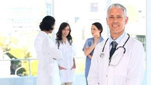 Smiling mature doctor standing upright in front of his team