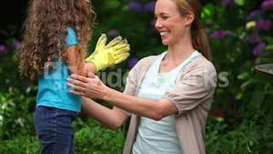 Mother and daughter wearing garden gloves