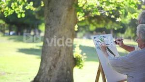 Retired couple painting a tree together on canvas