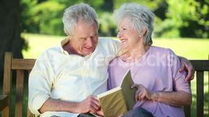Retired couple reading a book together
