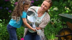 Mother and daughter watering flowers together