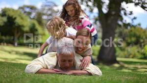 Family lying on a fathers back