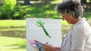 Mature woman painting on a canvas