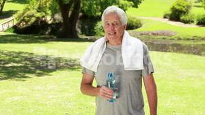 Happy mature man drinking water after doing sport