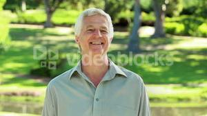 Peaceful mature man standing while looking at the camera