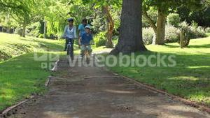 Smiling family riding bikes on a pathway