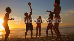 Young people playing beach ball