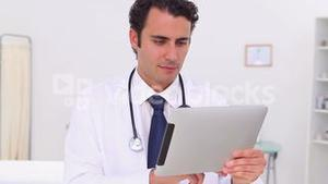 Serious doctor using his tablet pc