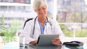 Smiling practitioner holding a tablet computer