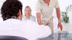 Couple coming and giving a handshake to a doctor