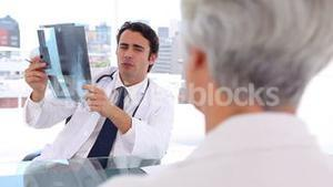 Serious doctor holding an xray in front of his patient