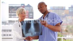 Serious doctor looking at an xray with a nurse