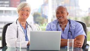Smiling doctor talking with a nurse in front of a laptop