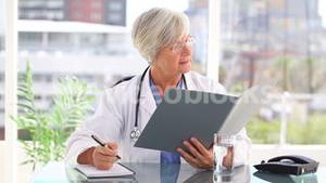 Smiling mature doctor looking at files