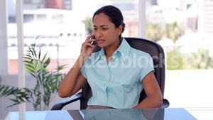 Serious woman picking up her mobile phone