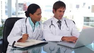 Doctor using a laptop while his colleague is taking notes