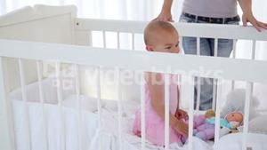 Woman putting her baby girl in a cradle