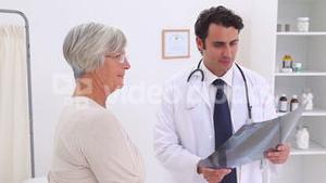 Doctor holding a chest xray and gives a handshake to a patient