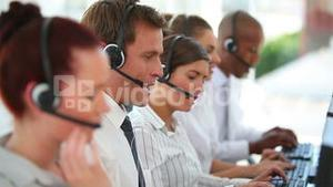 A large business team wearing headsets
