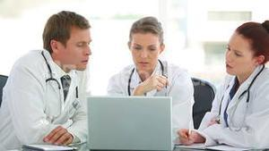 Three medical doctors watching the laptop
