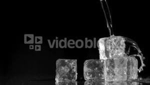 Water being poured in super slow motion onto ice cubes