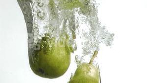 Pears in super slow motion falling in the water
