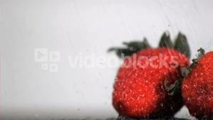 Water in super slow motion falling on red fruits