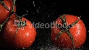 Raindrops in super slow motion falling on tomatoes