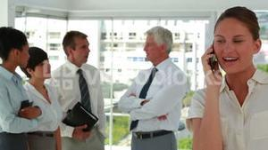 Business people talking with woman on the phone in foreground