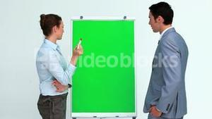 Two business people talking in front of a board