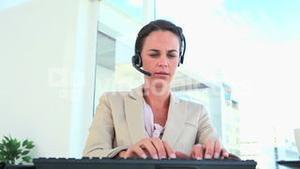 Businesswoman working and speaking with a headset