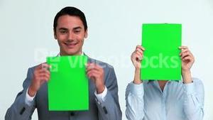 Business people hiding their face with a sign