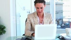 Happy woman working with laptop and picking up the phone