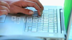 Close up on someoness hands typing on a laptop