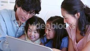 Family laughing while using a tablet computer